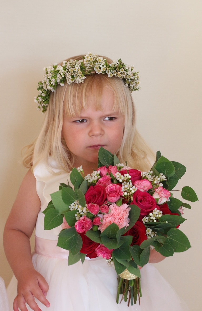 a flower girl holding a small bouquet