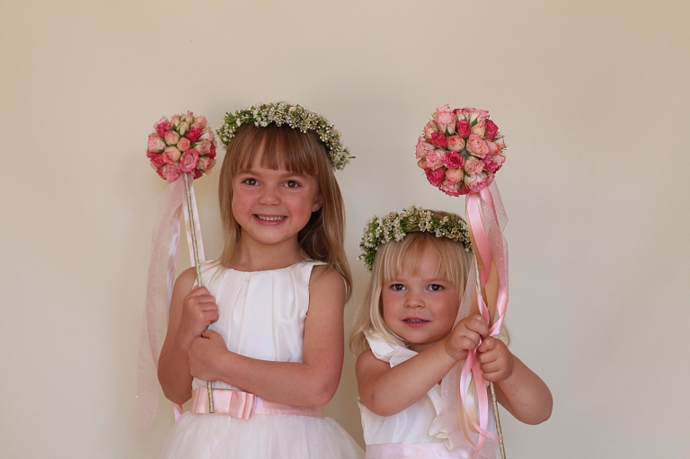 two cute flower girls hold pink flower wands with ribbon