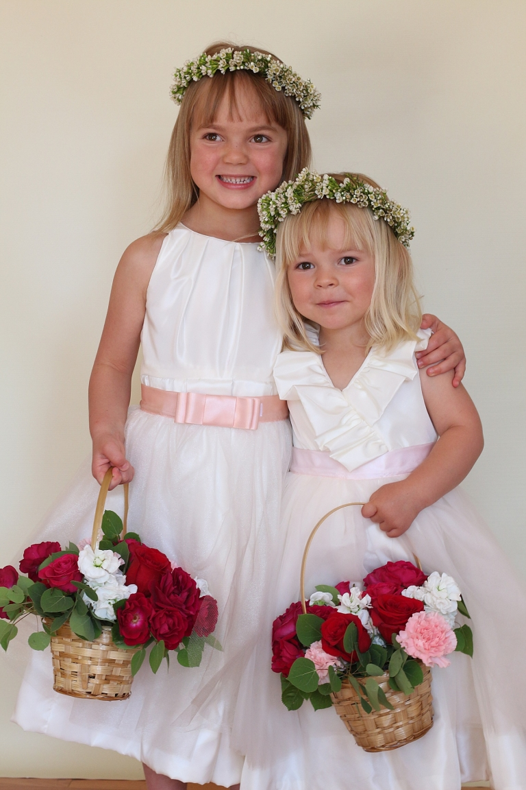 two flower girls smiling holding baskets of flowers