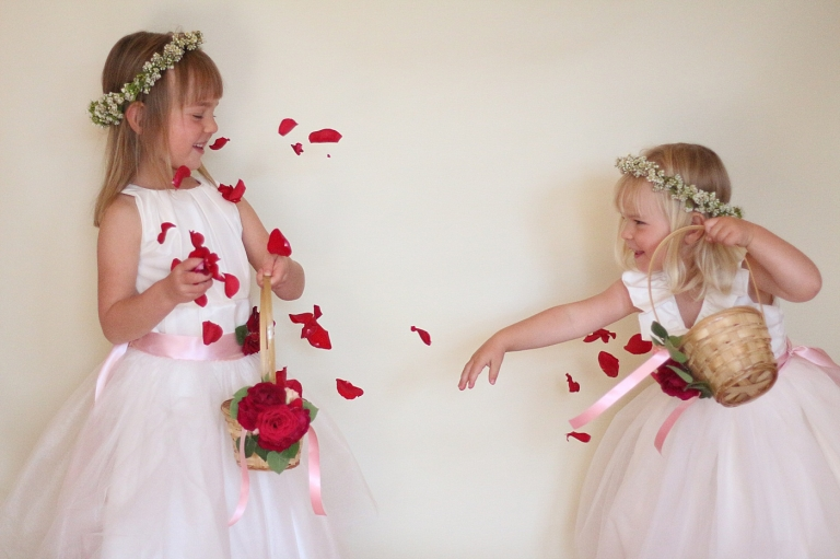 a flower girl thropwing red rose petals at another flower girl