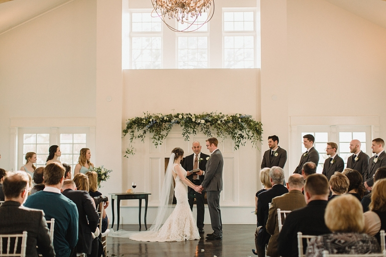 greenery and flowers on a mantle at a wedding ceremony