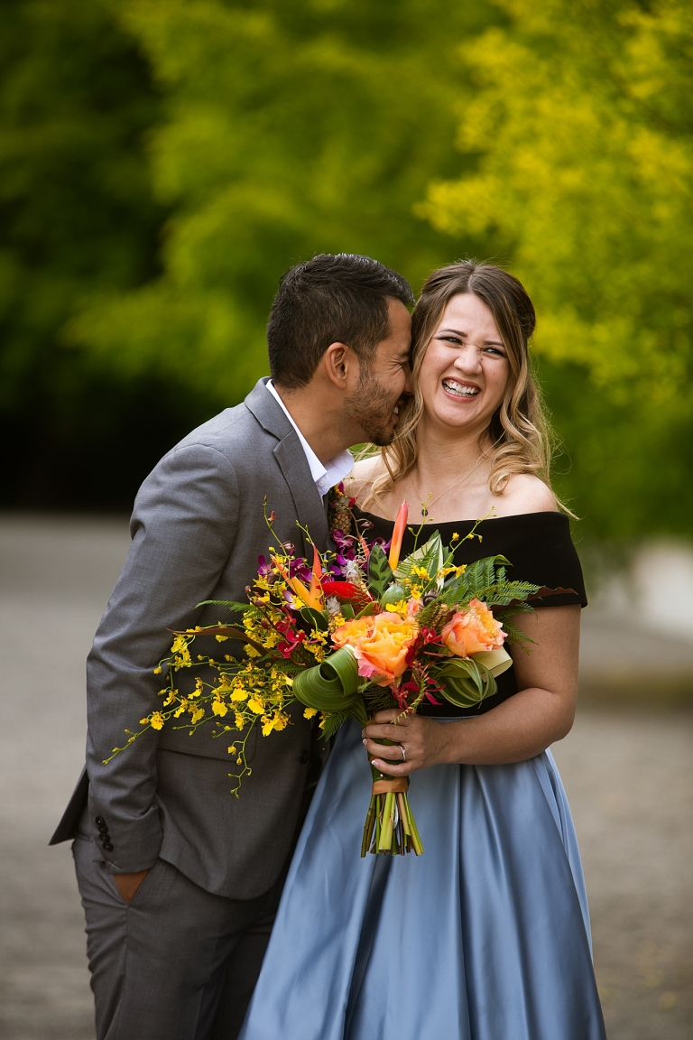 groom kissing bride holding colorful bouquet