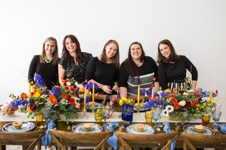 five women at a beautifully set dinner table with colorful florals