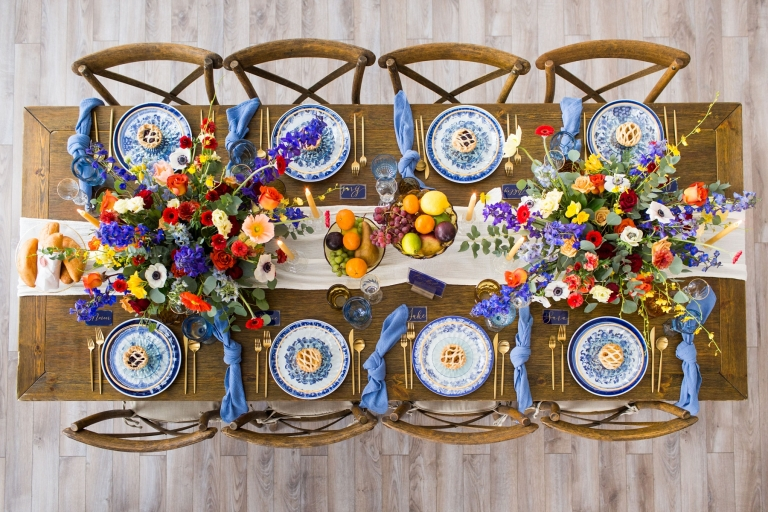 long dinner table with fancy place settings and colorful flowers