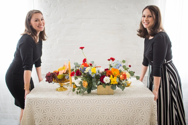 two women moving a table with colorful flowers