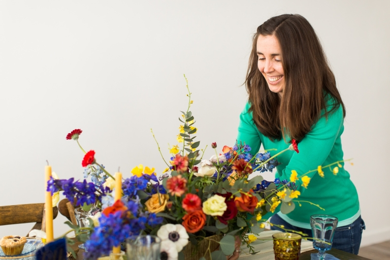 a lady in a geen top puts a floral arrangement on a table