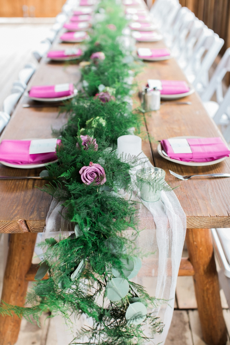 floral garland along table with lavender napkins