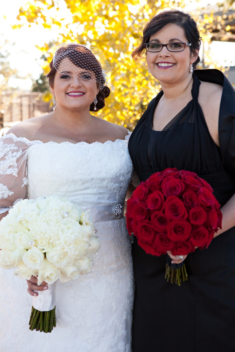 a bride and her bridesmaid holding red and white bouquets