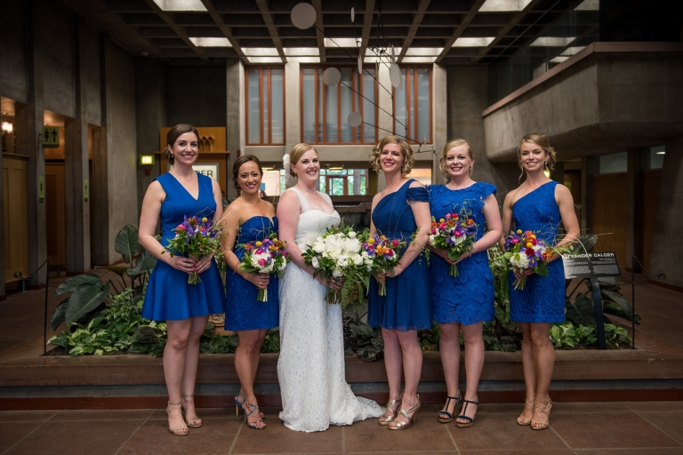 bridesmaids in blue dresses with colorful bouquets